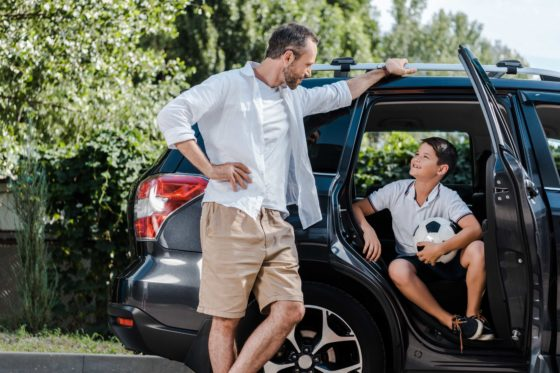 Father and son at car with soccer ball