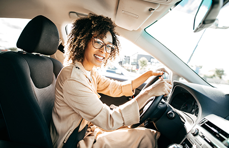 Woman with glasses driving a car