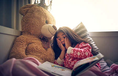 girl storytelling with bear