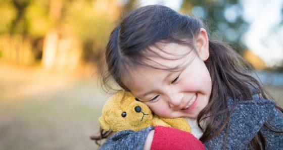 girl holding toy bear