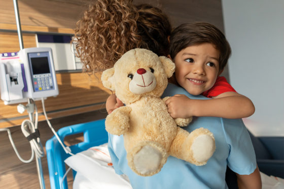 smiling boy in hospital holding teddy bear