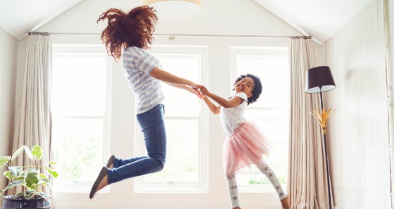 mom and daughter jumping in home