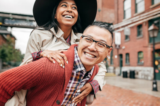 smiling woman riding piggy back on smiling man