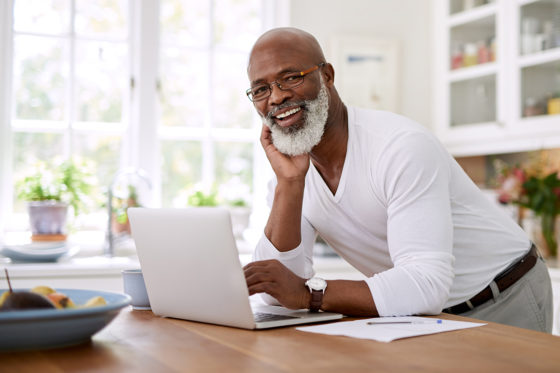 older smiling gentleman using laptop computer on kitchen counter