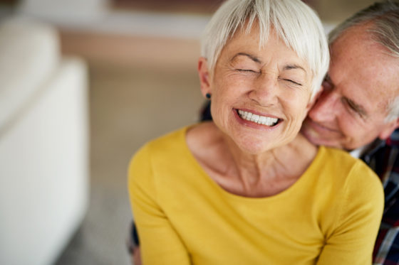 mature grinning woman with eyes closed in yellow