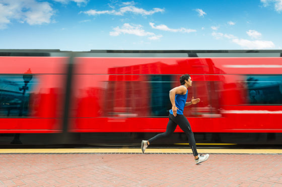 Man running aside a red train