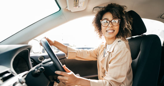 A young woman with glasses driving