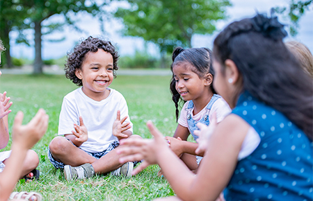 children sitting on grass playing