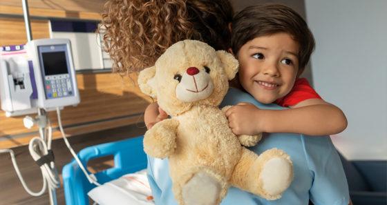 smiling boy in hospital holding teddy bear