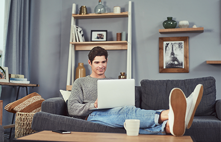 man on couch using laptop