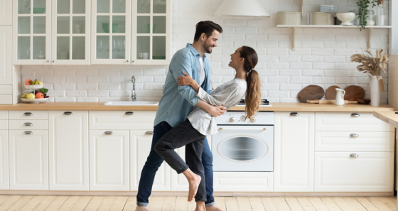happy couple dancing in home kitchen