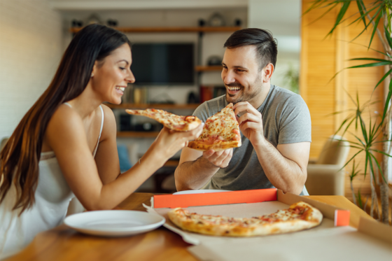 Happy couple eating pizza at home