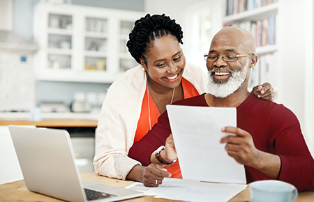 Couple in front of computer smiling at paper