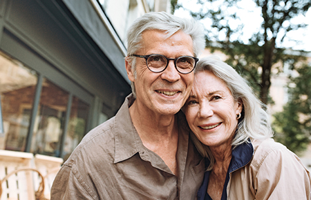 Elderly couple in front of house