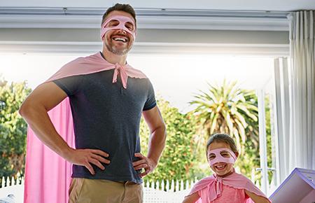 Dad and daughter dressed as superheroes