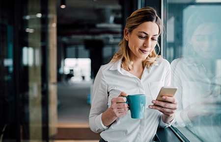 Woman with coffee looking at phone
