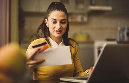 Woman at computer looking at bill