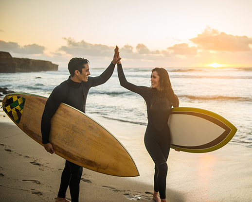 Woman and Man surfers High Fiving